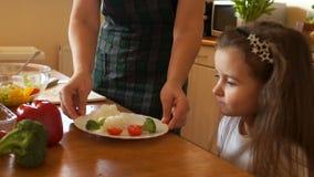 Gezond voedsel thuis Gelukkige familie in de keuken Moeder en kind de dochter bereidt de groenten voor stock videobeelden