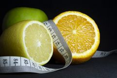 Gezond voedsel: vers fruit en het meten van band op zwarte achtergrond royalty-vrije stock afbeeldingen