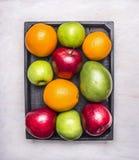 Gezond voedsel vers rijp fruit, appelen van verschillende verscheidenheden, sinaasappelen, mango's in houten doosgrens, houten ru royalty-vrije stock foto's