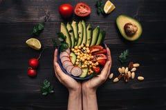 Gezond voedselconcept Handen die gezonde salade met kikkererwt en groenten houden Veganistvoedsel Vegetarisch dieet Royalty-vrije Stock Afbeelding