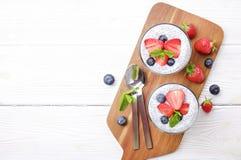 Gezond voedzaam veganist superfood dessert met organische bessen en chiazaden met verschillende dienende opties op houten lijst Royalty-vrije Stock Foto's