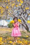 Gezond Weinig leuk meisje in roze kleding met gele bloemen stock foto's