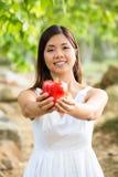 Gezonde Aziatische vrouw in de de witte bloemen en vruchten van de kledingsholding bij groen park Stock Afbeeldingen