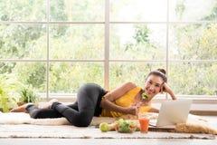 Gezonde Aziatische vrouw die op de vloer liggen die salade eten en camera bekijken stock afbeeldingen