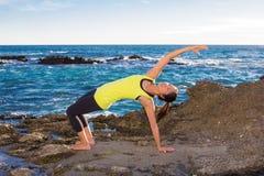 Gezonde Aziatische vrouw het praktizeren yoga bij strand die gele bovenkant dragen Stock Foto
