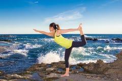 Gezonde Aziatische vrouw het praktizeren yoga bij strand die gele bovenkant dragen Stock Afbeelding