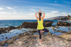 Gezonde Aziatische vrouw het praktizeren yoga bij strand die gele bovenkant dragen Royalty-vrije Stock Afbeeldingen