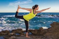 Gezonde Aziatische vrouw het praktizeren yoga bij strand die gele bovenkant dragen Royalty-vrije Stock Foto's