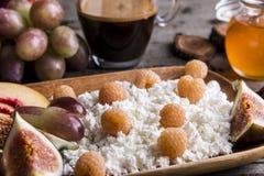 Gezonde breakfastHomemadekwark, frambozen, fig., perzik, honing, koffie bij het dienen van raad over rustieke houten stock foto's