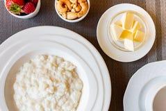 Gezonde de havermoutpapkom van de ontbijtrijst met bessen en noten op het lijst, hete en gezonde ontbijtvoedsel, hoogste mening stock foto