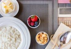 Gezonde de havermoutpapkom van de ontbijtrijst met bessen en noten op het lijst, hete en gezonde ontbijtvoedsel, hoogste mening stock foto's