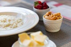 Gezonde de havermoutpapkom van de ontbijtrijst met bessen en noten op het lijst, hete en gezonde ontbijtvoedsel, zijaanzicht stock afbeelding