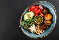 Gezonde de komschotel van Boedha met avocado, tomaat, kaas, kikkererwt, verse arugulasalade, aardappelen in de schil en sauspesto royalty-vrije stock foto