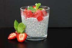 Gezonde Dessertpudding Chia Seeds in Yoghurt, Yoghurt en Aardbeien en Munt in de Glaskommen Zwarte achtergrond royalty-vrije stock foto