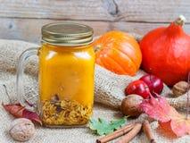 Gezonde die Ontbijta smoothie van pompoen en appelen met granola wordt gemaakt en noten in een metselaarkruik Stock Foto's