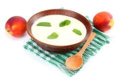 Gezonde die perzikyoghurt met perzik gruit en muntbladeren op witte achtergrond worden geïsoleerd Royalty-vrije Stock Foto