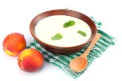 Gezonde die perzikyoghurt met perzik gruit en muntbladeren op witte achtergrond worden geïsoleerd Royalty-vrije Stock Foto's