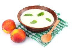 Gezonde die perzikyoghurt met perzik gruit en muntbladeren op witte achtergrond worden geïsoleerd Stock Afbeeldingen