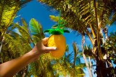 Gezonde drank op een Caraïbisch strand Ananas en kokosnoot handbediend op strand onder palmen stock afbeelding