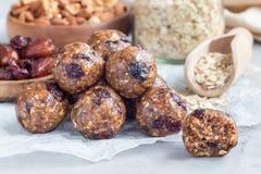 Gezonde eigengemaakte energieballen met Amerikaanse veenbessen, noten, data en gerolde haver op horizontaal perkament, royalty-vrije stock fotografie