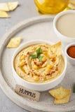 Gezonde eigengemaakte hummus met olijfolie en spaanders stock foto