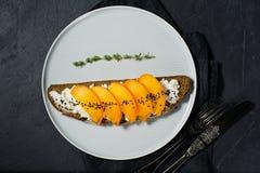 Gezonde evenwichtige voedselsandwich met dadelpruim en zachte kaas op zwarte achtergrond stock afbeelding