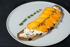 Gezonde evenwichtige voedselsandwich met dadelpruim en zachte kaas op zwarte achtergrond royalty-vrije stock afbeelding
