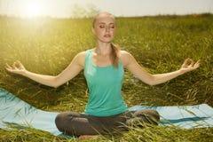Gezonde geschikte blonde jonge vrouw die op de aard met ogen mediteren Royalty-vrije Stock Foto