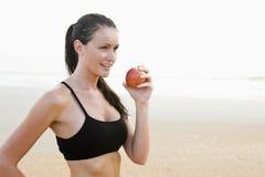 Gezonde geschikte jonge vrouw die op strand appel eet stock foto's