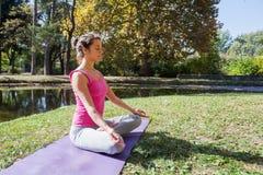 Gezonde Geschikte Vrouw die Yogameditatie in Aard doen royalty-vrije stock afbeelding