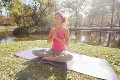Gezonde Geschikte Vrouw die Yogameditatie in Aard doen stock foto