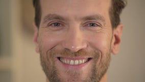 Gezonde glimlach van de knappe jonge mens die camera, mannelijk gezichtsclose-up onderzoeken stock videobeelden