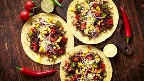 Gezonde graantortilla's met geroosterd rundvlees, verse hete peper, kaas, tomaten stock videobeelden