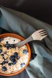 Gezonde granola van de ontbijthaver met verse bosbessen, de bessen en de melk in een klei werpen over donkere grungeoppervlakte H Royalty-vrije Stock Afbeelding
