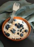 Gezonde granola van de ontbijthaver met verse bosbessen, de bessen en de melk in een klei werpen over donkere grungeoppervlakte H Stock Afbeelding