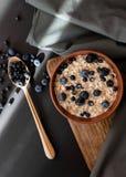 Gezonde granola van de ontbijthaver met verse bosbessen en de bessen in een klei werpen over donkere grungeoppervlakte Royalty-vrije Stock Foto's