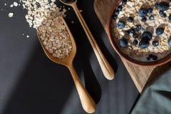 Gezonde granola van de ontbijthaver met verse bosbessen en de bessen in een klei werpen over donkere grungeoppervlakte Hoogste me Stock Fotografie