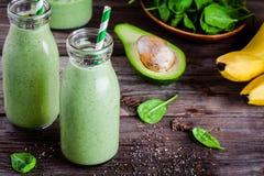 Gezonde groene smoothie met banaan, spinazie, avocado en chiazaden in glasflessen Royalty-vrije Stock Afbeeldingen