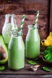 Gezonde groene smoothie met banaan, spinazie, avocado en chiazaden in glasflessen Stock Foto