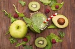 Gezonde groene smoothie met banaan, spinazie, avocado en kiwi in een glasflessen op een plattelander Royalty-vrije Stock Fotografie