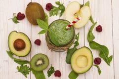 Gezonde groene smoothie met banaan, spinazie, avocado en kiwi in een glasflessen op een plattelander Royalty-vrije Stock Afbeelding