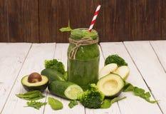 Gezonde groene smoothie met banaan, spinazie, avocado en komkommer in een glasflessen op een plattelander Royalty-vrije Stock Afbeeldingen