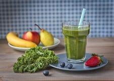 Gezonde groene smoothie met boerenkool, aardbeien, bosbessen, banaan, appel, peer en honing in een glas tegen een rustiek hout ba stock afbeelding