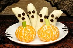 Gezonde Halloween-banaanspoken en oranje pompoenen Stock Fotografie