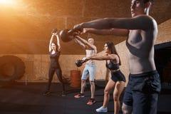 Gezonde jonge atleten die oefeningen met kettlebells doen, bij geschiktheidsstudio Royalty-vrije Stock Afbeelding