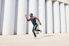 Gezonde jonge atletische mens die bij de weg lopen Stock Fotografie