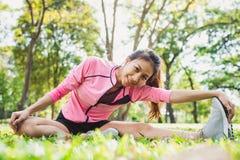 Gezonde jonge Aziatische vrouw die bij park uitoefenen Geschikte jonge vrouw die opleidingstraining in ochtend doen Royalty-vrije Stock Foto