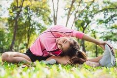 Gezonde jonge Aziatische vrouw die bij park uitoefenen Geschikte jonge vrouw die opleidingstraining in ochtend doen Stock Fotografie