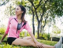 Gezonde jonge Aziatische vrouw die bij park uitoefenen Geschikte jonge vrouw die opleidingstraining in ochtend doen Royalty-vrije Stock Afbeelding