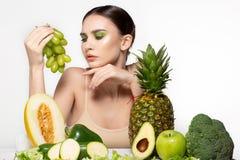 Gezonde jonge donkerbruine vrouw die groene druiven in haar hand, vruchten en groenten op de lijst, studiofoto bekijken stock foto